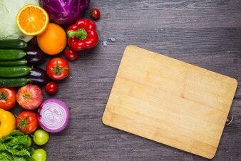 Mesa con verduras y una tabla de cortar