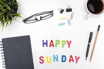 Mesa de escritorio de oficina con la palabra de domingo feliz
