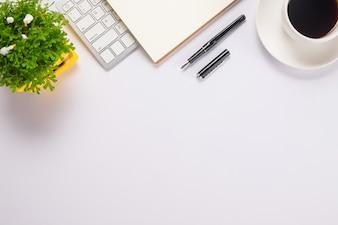 Mesa de escritorio de oficina con lápiz, teclado en el bloc de notas, taza de café y flores. Vista superior con espacio de copia (enfoque selectivo).