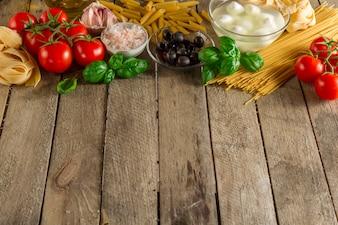 Mesa de madera con albahaca y otros ingredientes