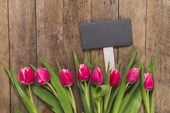 Mesa de madera con letrero y tulipanes en fila