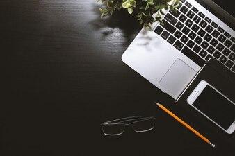Mesa de trabajo negro con ordenador portátil, smartphone y gafas