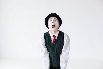 Mime en gorra de sombrero negro y chaleco sobre fondo blanco
