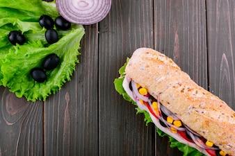 Mira desde arriba en la ensalada verde, piezas de cebolla azul y sándwich integral en la mesa de madera oscura