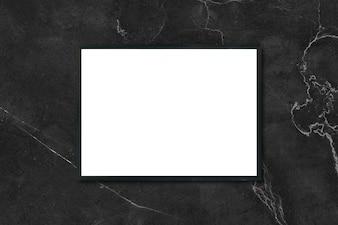 Mock up marco cartel en blanco colgando de mármol negro en la pared de la habitación - se puede utilizar la maqueta para el montaje de los productos de visualización y el diseño de diseño visual clave.