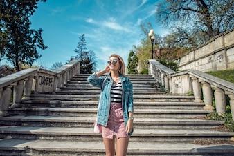 Modelo de moda hermosa posando en las escaleras llevaba falda rosada, rayas y chaqueta de mezclilla