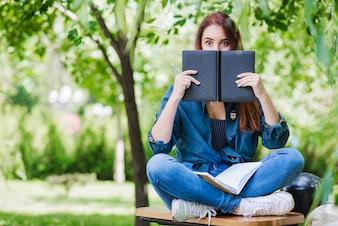 Modelo posando con libros en el parque