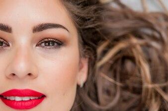 Modelo sensual de la mujer con el pelo azotado por el viento pelo moreno sobre fondo gris claro. Peinado largo brillante de la salud. Belleza y cuidado del cabello. Maquillaje natural de la manera
