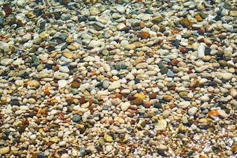 Montón de piedras de colores en la orilla del mar