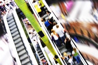 Mucha gente en la escalera mecánica