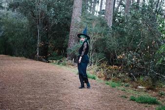 Muchacha en sombrero de la bruja que se coloca en camino