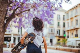 Muchacha que sostiene el monopatín que camina bajo árboles florecientes
