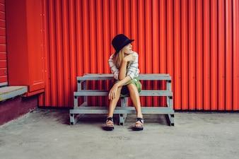 Muchacha rubia en un sombrero. Foto de la calle. Una hermosa niña vistiendo ropa casual está sonriendo misteriosamente. Estilo vintage