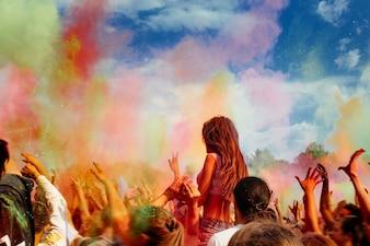 Muchas personas tirando pintura en polvo hacia el aire