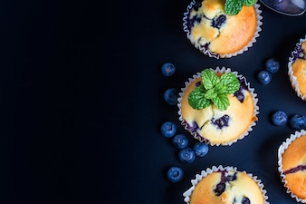 Muffins de arándanos con el azúcar en polvo y bayas frescas