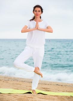 Mujer 20-30 años de edad se encuentra y practicar la meditación en camiseta blanca en la playa.