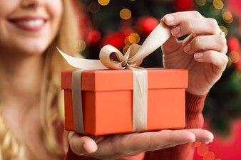 Mujer abriendo un regalo naranja