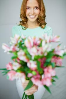 Mujer alegre con flores desenfocadas primer plano