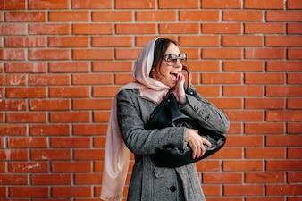 Mujer alegre con pared de ladrillos de fondo
