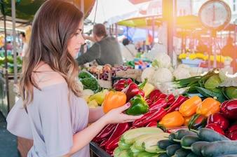 Mujer alegre elegir el pimentón verde y rojo en el supermercado. Compras. Mujer que elige la fruta de la comida bio pimienta paprica en el mercado verde