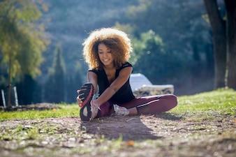 Mujer alegre estirando su pierna en el suelo