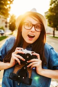 Mujer alegre que se divierte en la ciudad con gafas y sombrero
