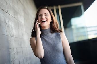 Mujer alegre riendo y hablando por teléfono móvil