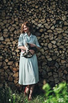 Mujer apoyada en una pared con un vestido largo