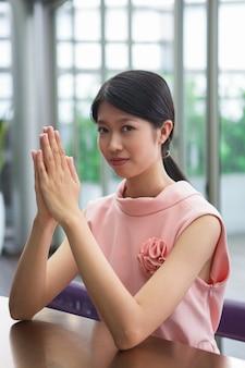 Mujer asiática seria con las manos juntas