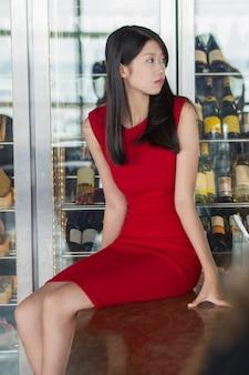 Mujer asiática serio joven en vestido rojo en barra