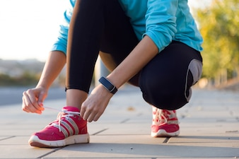 Mujer atleta atar cordones para correr.