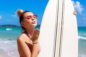 Mujer atractiva con gafas de sol dando un beso del aire