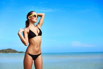 Mujer atractiva en bikini disfrutando de un día soleado