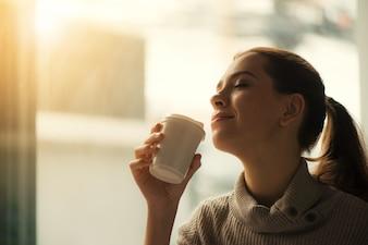Mujer beber café en casa con la salida del sol fluyendo a través de la ventana y crear llamarada en la lente.