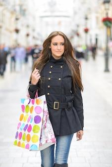Mujer bonita con bolsas de la compra en la calle