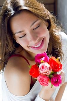 Mujer bonita con flores en casa