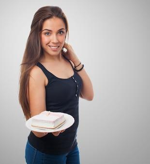 Mujer bonita que ofrece un poco de torta