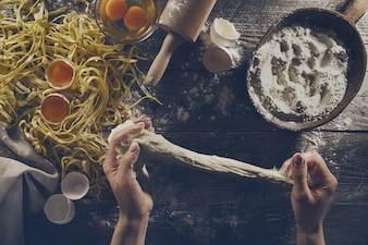 Mujer cocinar manos preparando sabrosas caseras italianas clásicas pastas en mesa de madera. De cerca. Vista superior. Viraje.