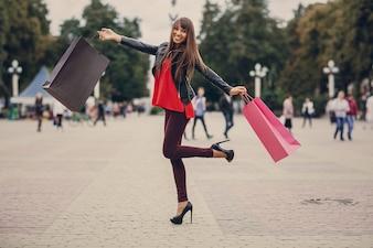 Mujer con bolsas de la compra y pierna levantada