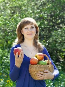 Mujer con cestas de manzanas cosechadas
