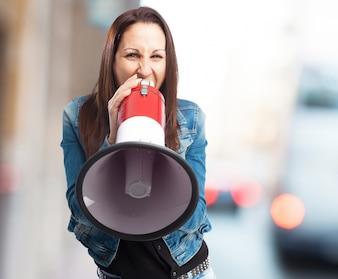 Mujer con chaqueta vaquera gritando por un megáfono