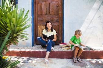 Mujer con el libro y el niño en el pórtico