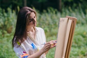Mujer con el pelo suelto pintando un lienzo