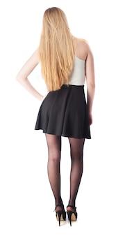 Mujer con falda y tacones de espaldas y una mano en la cadera