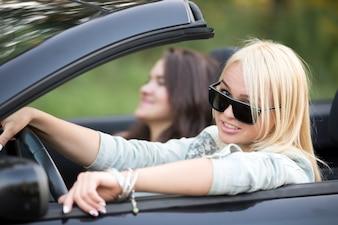 Mujer con gafas de sol conduciendo su coche
