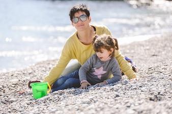 Mujer con gafas de sol jugando con su hija en la playa
