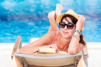 Mujer con gafas de sol posando con un libro