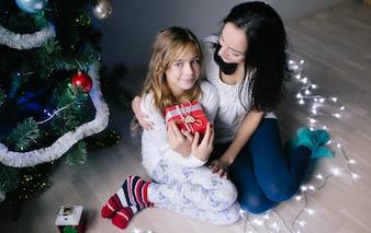 Mujer con la hija en el árbol de navidad