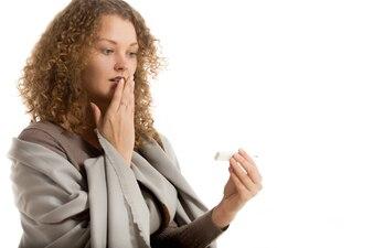 Mujer con la mano en la boca mirando el termómetro