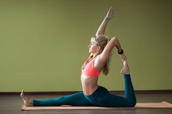 Mujer con las piernas abiertas estirando su espalda